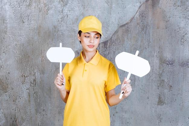 Agente de serviço feminino em uniforme amarelo segurando balcões de informações com as duas mãos