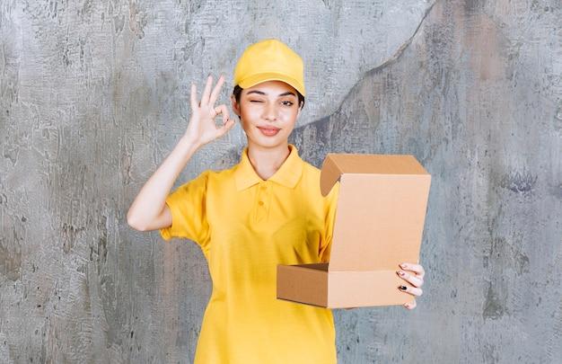 Agente de serviço feminino em uniforme amarelo segurando uma caixa de papelão aberta e mostrando um sinal positivo com a mão