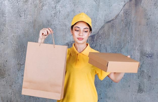 Agente de serviço feminino em uniforme amarelo, segurando uma caixa de papelão e um saco de papel.