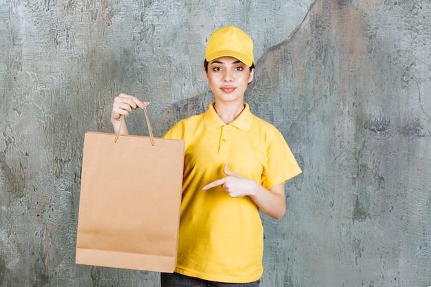 Agente de serviço feminino em uniforme amarelo, segurando uma sacola de compras.