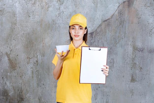 Agente de serviço feminino em uniforme amarelo, segurando uma tigela de plástico para viagem e dando a lista de clientes para assinatura.