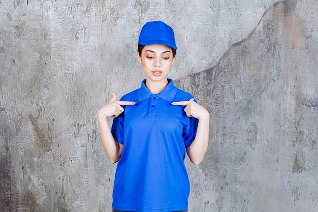 Agente de serviço feminino em uniforme azul, apontando para si mesma.
