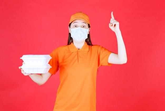 Agente de serviço feminino em uniforme de cor laranja e máscara segurando dois pacotes de comida para viagem, pensando e tendo uma boa ideia.