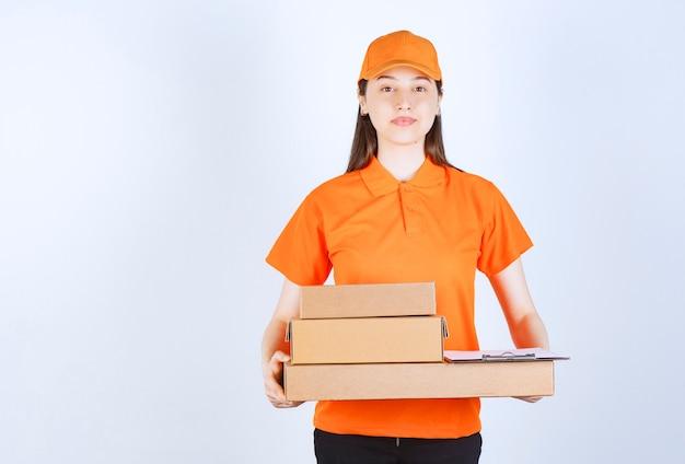 Agente de serviço feminino em uniforme de cor laranja entregando várias caixas de papelão.