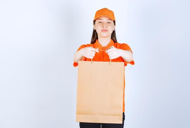 Agente de serviço feminino em uniforme de cor laranja, segurando uma sacola de compras e apresentando-a ao cliente.