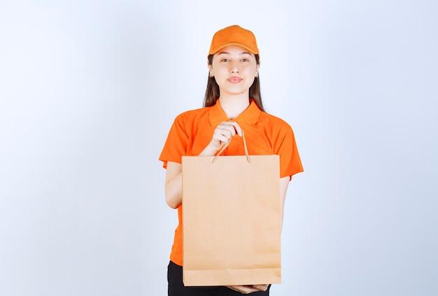 Agente de serviço feminino em uniforme de cor laranja, segurando uma sacola de papelão e apresentando-a ao cliente.