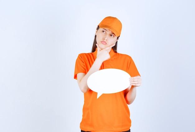 Agente de serviço feminino em uniforme laranja segurando um quadro oval de informações e parece confusa e desmotivada.