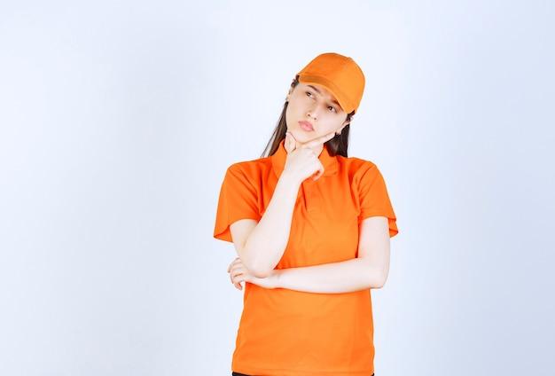 Agente de serviço feminino usando dresscode cor laranja e parece pensativo.