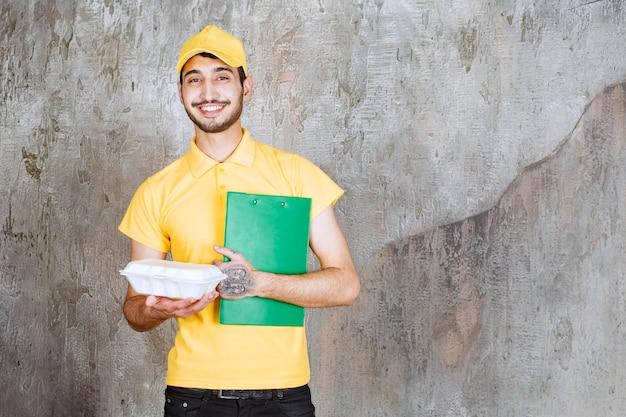 Agente de serviço masculino de uniforme amarelo, segurando uma caixa branca para viagem e a lista de endereços.