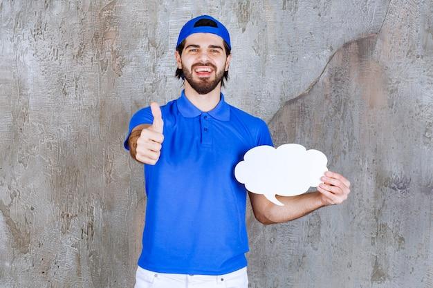 Agente de serviço masculino de uniforme azul, segurando uma placa de informações de forma de nuvem em branco e mostrando um sinal positivo com a mão.