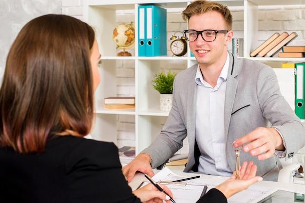 Agente de vendas dando as chaves para o cliente