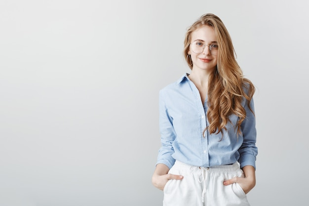 Agente de viagens ouvindo os desejos dos clientes. retrato de uma mulher de negócios europeia bonita de blusa azul e óculos, segurando as mãos nos bolsos e sorrindo, sendo simpática e educada sobre a parede cinza