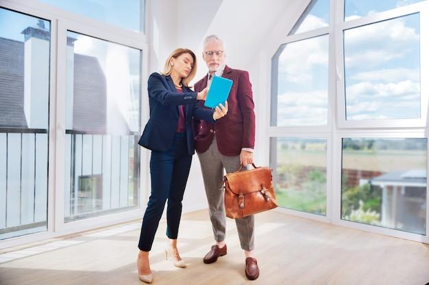 Agente do estado. próspera corretora imobiliária profissional consultando seu próspero cliente rico usando seu pequeno tablet branco