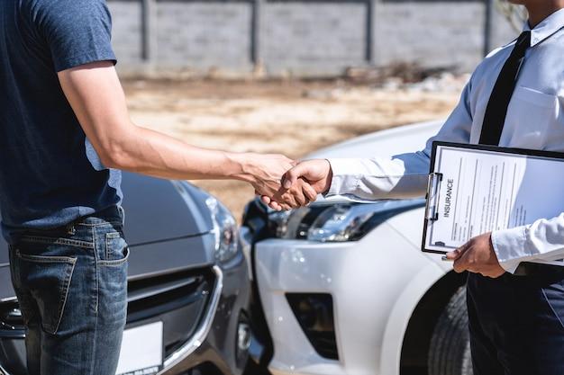 Agente e cliente apertando as mãos após acordo em reivindicação de seguro, avaliado examinando acidente de carro