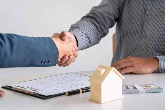 Agente imobiliário agitando as mãos com um cliente
