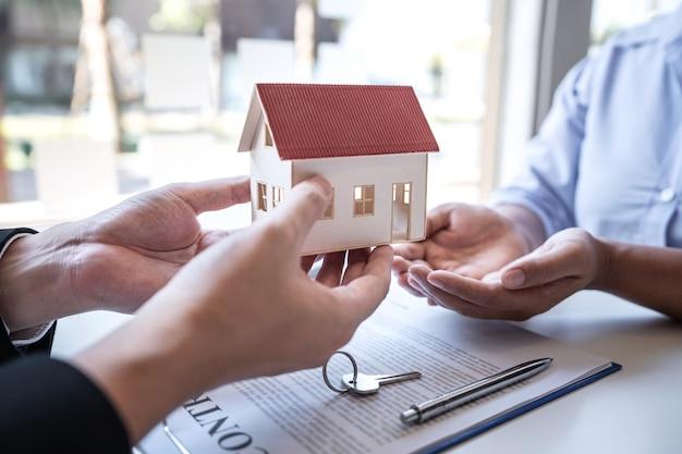 Agente imobiliário apresentando empréstimo imobiliário e dando modelo de casa ao cliente
