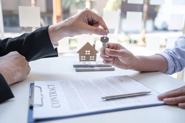 Agente imobiliário apresentando empréstimo residencial e dando as chaves ao cliente