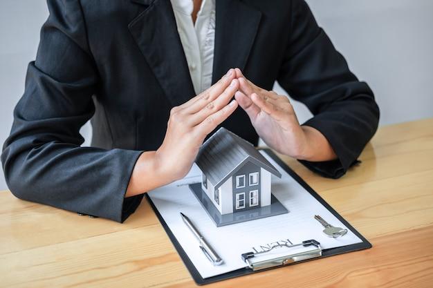 Agente imobiliário cobrindo modelo de casa com as mãos