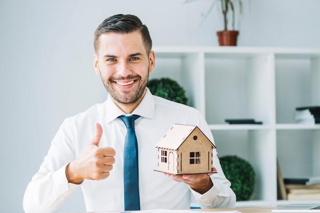 Agente imobiliário com casa de brinquedo gesticulando polegar-up