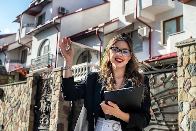 Agente imobiliário com chave contra casa nova. mudança de casa ou aluguel de propriedade