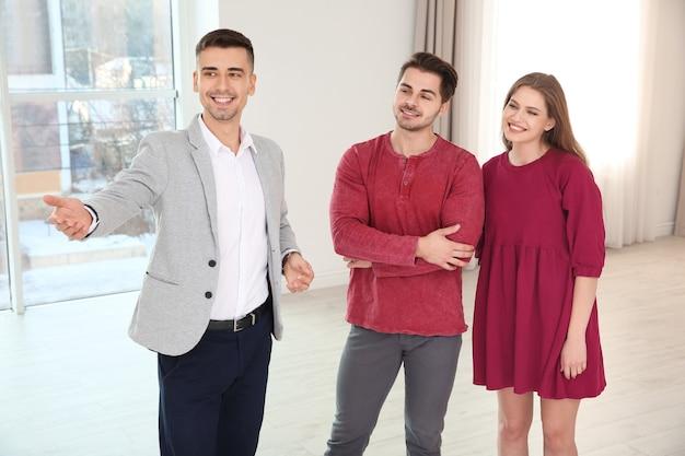Agente imobiliário com clientes em casa nova