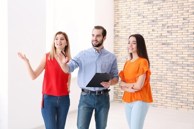 Agente imobiliário com estagiário mostrando apartamento ao cliente