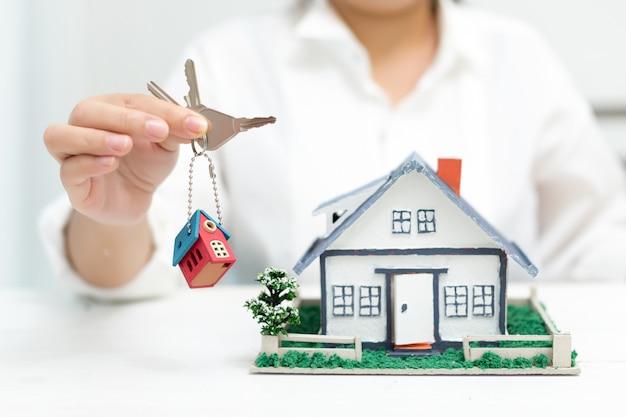 Agente imobiliário com modelo de casa e chaves