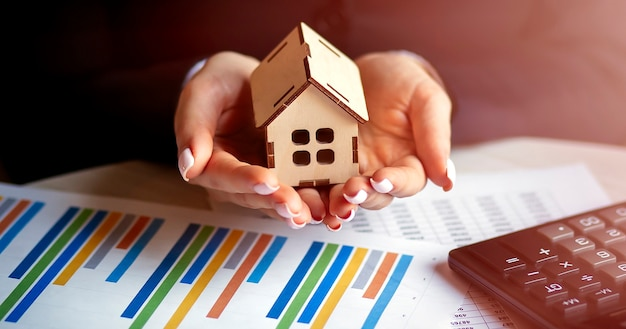 Agente imobiliário com modelo de casa e gráfico sobre a mesa