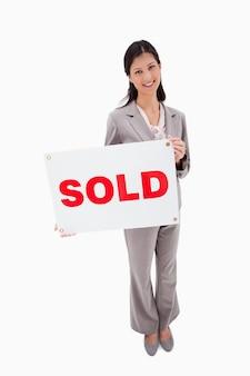Agente imobiliário com sinal vendido