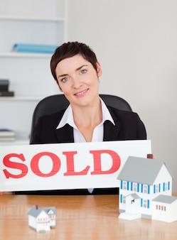 Agente imobiliário com um painel vendido e casas de miniaturas