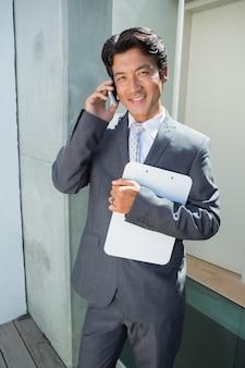 Agente imobiliário confiante de pé na porta da frente no telefone