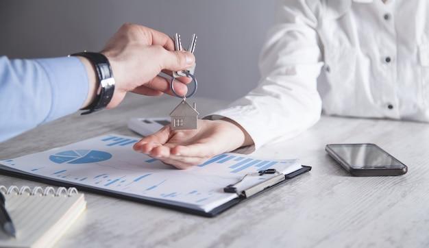 Agente imobiliário dando chaves ao cliente.