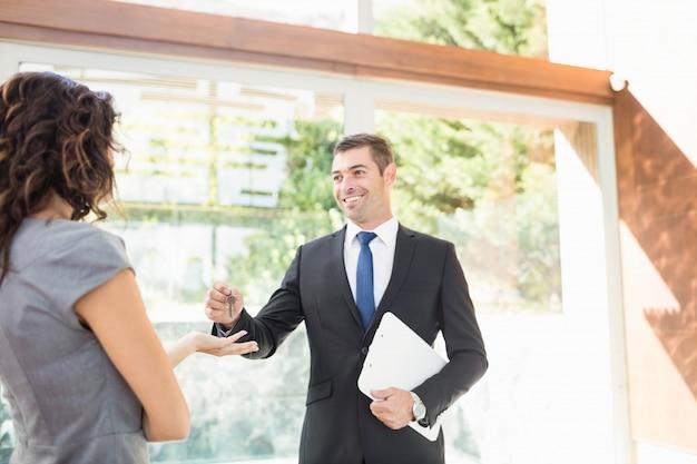 Agente imobiliário dando chaves para novos proprietários