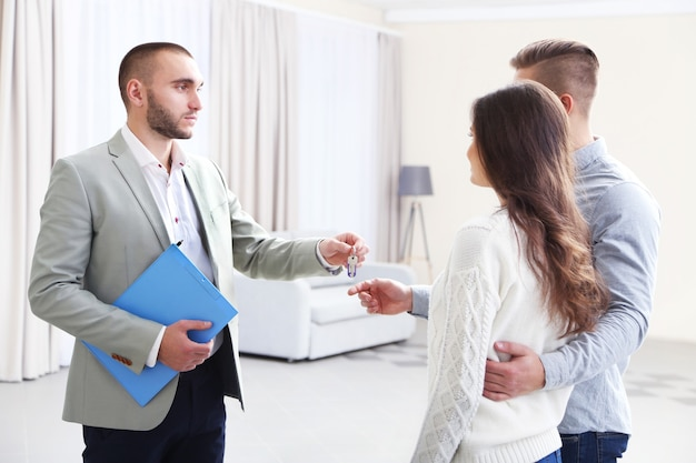 Agente imobiliário dando chaves para o casal, sobre fundo claro
