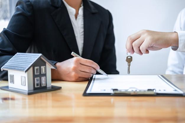 Agente imobiliário dando uma chave para um cliente