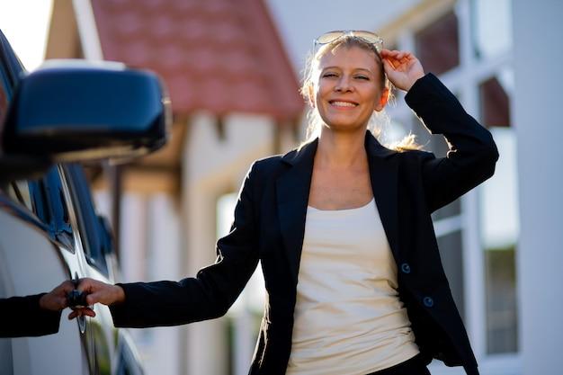 Agente imobiliário de mulher bonita de terno e carro preto no fundo da casa