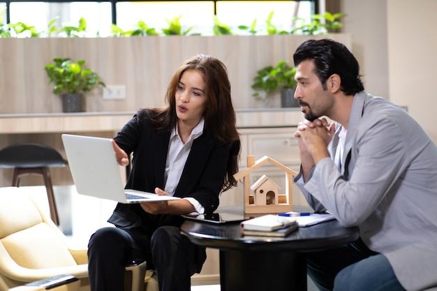 Agente imobiliário de mulher bonita, oferecendo e mostrando uma apresentação online no laptop no escritório para um homem bonito.