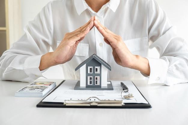 Agente imobiliário de mulher de negócios com gesto protetor do pequeno modelo para casa com as mãos.