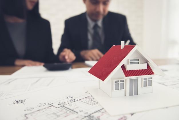 Agente imobiliário discutindo o trabalho com plantas e modelo de casa em cima da mesa