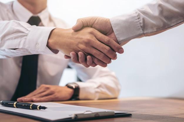 Agente imobiliário e cliente apertando as mãos