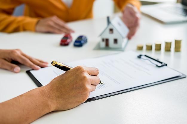 Agente imobiliário e cliente assinando contrato para comprar casa, seguro ou empréstimo imobiliário.