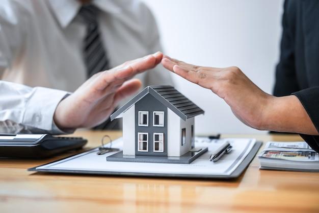 Agente imobiliário e cliente cobrindo modelo de casa pequena e proteção pelas mãos