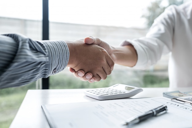 Agente imobiliário e clientes apertando as mãos após a assinatura do contrato