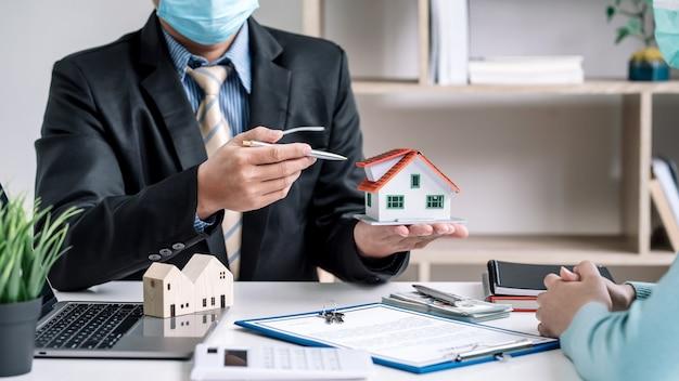Agente imobiliário em casa para os clientes concordarem em negociar no escritório usando máscaras.