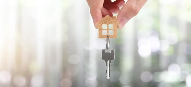 Agente imobiliário entregando as chaves de uma casa em mãos e moedas