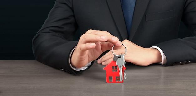 Agente imobiliário entregando as chaves de uma casa em mãos