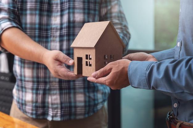 Agente imobiliário entregando um modelo de casa com seu cliente após o negócio de vedação
