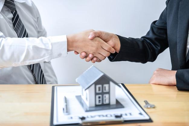 Agente imobiliário está apertando as mãos após um bom negócio e dando casa, chaves para o cliente depois de discutir e assinar contrato para comprar casa com o formulário de inscrição aprovado