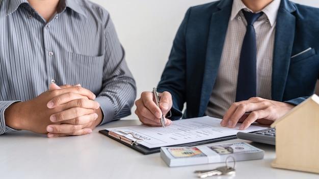 Agente imobiliário está apresentando empréstimo à habitação e dando casa ao cliente após assinar contrato para comprar