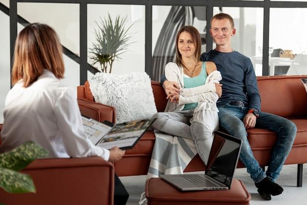 Agente imobiliário falando com casal